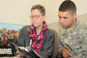 Sarah L. Hood, the Journalism Preparatory Course instructor at the Defense Information School on Fort Meade, discusses a magazine article April 8,2016, with Army Pvt. Hubert Delany, who completed J-Prep and is scheduled to graduate from the Basic Public Affairs Specialist Course at DINFOS. J-Prep is an informal 16-day class that focuses on English essentials. Although it's not a requirement for everyone, J-Prep is designed to build confidence and improve students' chances for success in BPASC.