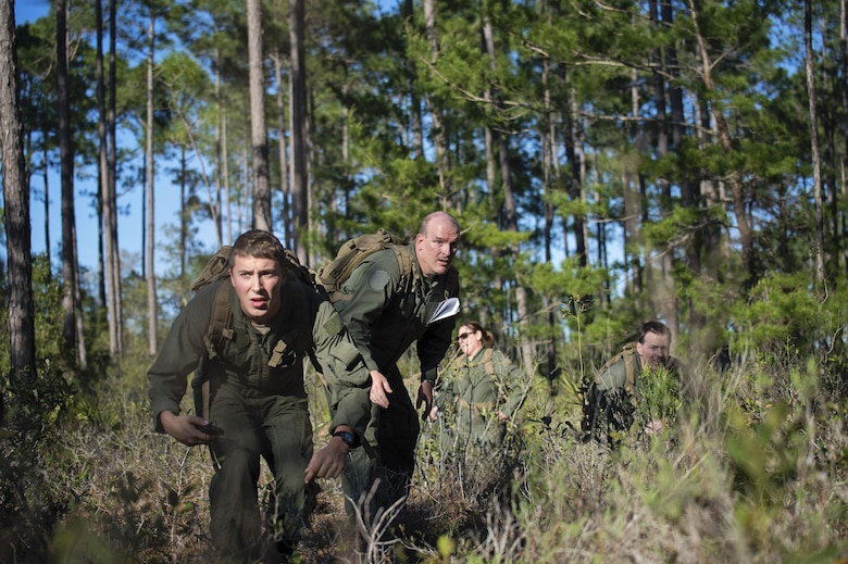 Senior Airman Jake Voshell (left), a loadmaster with the 709th Airlift Squadron, leads his team through the simulated evasion portion of combat training, April 2, 2016, at Naval Air Station Pensacola, Fla. Reservists from Dover Air Force Base, Del., in the 512th Airlift Wing, conducted an off-station training exercise, March 29 to April 3, to ensure they are current in all their deployment requirements. (U.S. Air Force photo/Capt. Bernie Kale)