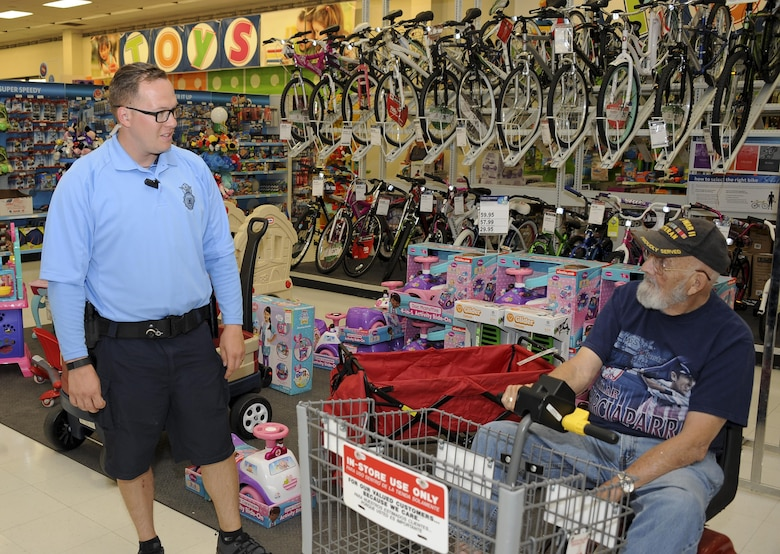 """U.S. Air Force Staff Sgt. Johnny Nunnes, 355th Security Forces Squadron base defense operations center controller, speaks with Tom Perrow, World War II veteran, about the bicycle patrol fleet at Davis-Monthan Air Force Base, Ariz., April 8, 2016. The fleet is a section within the 355th SFS that allows the """"defenders"""" not only more access to the base but more interaction with the D-M AFB community. (U.S. Air Force photo by Airman 1st Class Mya M. Crosby/Released)"""