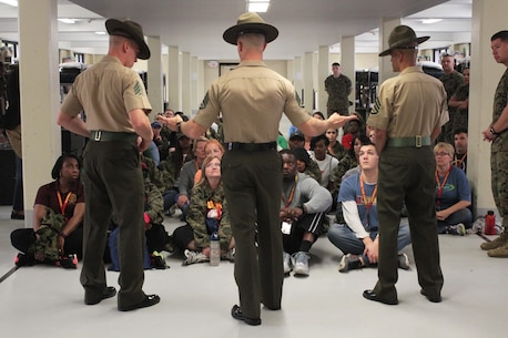 Drill Instructors Sgt Christopher Wade, Staff Sgt. Edward P. Underwood, and Staff Sgt. William Aguilar Castillo give educators a taste of what recruits go through when they first meet their Drill Instructors during receiving April 13, 2016, at Echo Company aboard Marine Corps Recruit Depot Parris Island, S.C. The teachers, coaches, and principals of Recruiting Stations Jacksonville and Montgomery participate in a three-day workshop designed to inform educators about military service and life in the Marine Corps. (Official Marine Corps photo by Cpl. Diamond N. Peden