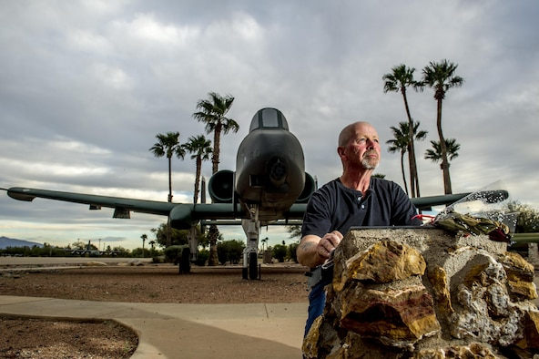 """Richard Brunt, 59, touches a memorial plaque, located in Heritage Park at Davis-Monthan Air Force Base, Ariz., March 5, 2016, which honors Captain Patrick B. Olson, who died on Feb. 27,1991, while trying to land a heavily damaged OA-10 during Operation Desert Storm. Brunt, who was Olson's crew chief, now works as a technician at the 309th Aerospace Maintenance and Regeneration Group, or the """"Boneyard"""" at D-M AFB, removing parts from decommissioned OA-10s to build inventories used by active A-10 Thunderbolt squadrons for maintaining their aircraft. (U.S. Air Force photo by J.M. Eddins Jr.)"""