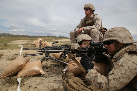 Marines with Company K, 3rd Battalion, 1st Marine Regiment, 1st Marine Division, conduct machine gun target engagement during live-fire training aboard Marine Corps Base Camp Pendleton, Calif., April 11, 2016. During the training, Marines fired an M249 Squad Automatic Weapon, which provides Marine fire teams the ability to quickly gain and maintain fire superiority, and M240 medium machine guns, which provide higher sustained rates of fire and longer effective range. The Marine in the foreground is sighting through his rifle combat optic so he can offer targeting adjustments to the machine gunner. (U.S. Marine Corps photo by Lance Cpl. Timothy Valero/ Released)