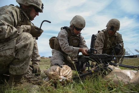 Corporal Jalen Freiberg [center], a machine gunner with Company K, 3rd Battalion, 1st Marine Regiment, 1st Marine Division, cleans an M249 Squad Automatic Weapon prior to conducting live-fire machine gun target engagement aboard Marine Corps Base Camp Pendleton, Calif., April 11, 2016. The M249 is counted on to provide the bulk of each Marine fire team's firepower while remaining maneuverable. (U.S. Marine Corps photo by Lance Cpl. Timothy Valero/ Released)