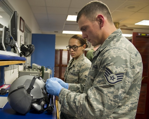Staff Sgt. Kody Crider and Airman 1st Class Cortney Oehlbeck, 325th Operations Support Squadron/43rd Fighter Squadron Aircrew Flight Equipment technicians, repair a pilot's helmet April 7, at the 43rd FS. The AFE shop is much like a detachment, comprised of a rotation of 325th OSS Airmen who spend a year at the shop inspecting and maintaining all of the 43rd FS F-22 Raptor pilots' life support equipment. (U.S. Air Force photo by Senior Airman Alex Fox Echols III/Released)