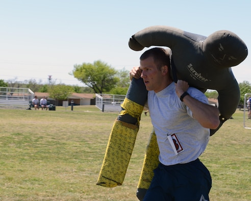 2nd Lt. Christopher Brown, 47th Student Squadron awaiting pilot training, carries a dummy across the football field at Laughlin Air Force Base, Texas, April 5, 2016. The dummy carry involved running a 100 yard sprint with a 75-pound dummy. (U.S. Air Force photo by Senior Airman Jimmie D. Pike)