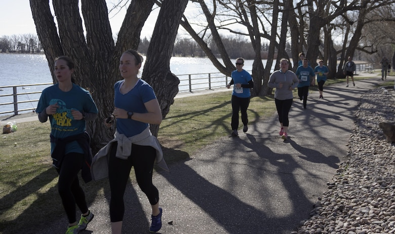 Runners follow the course around Sloan's Lake in Lion's Park, Cheyenne, Wyo., during the Sexual Assault Awareness 5- kilometer race April 9, 2016. More than 500 participants – Airmen, Soldiers, Guardsmen and community members – ran, walked and ruck-marched the course. (U.S. Air Force photo by Senior Airman Brandon Valle)
