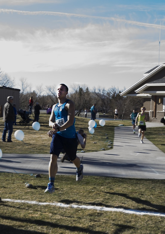 Senior Airman Eric Irizarry, 90th Medical Support Squadron, crosses the finish line of the Sexual Assault Awareness 5-kilometer race April 9, 2016, in Lion's Park, Cheyenne, Wyo. Irizarry finished second for males, with Senior Airman Aaron Hurtado, 790th Missile Security Forces Squadron, finishing in first place. (U.S. Air Force photo by Senior Airman Brandon Valle