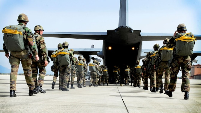 NATO service members prepare for a jump exchange prior to Saber Junction 16, April 5, 2016, at Aviano Air Base, Italy. The exercise involved the 173rd Airborne Brigade and 16 allied and European nations conducting land operations in a joint, combined environment and to promote interoperability with participating nations. (U.S. Air Force photo by Senior Airman Areca T. Bell/Released)