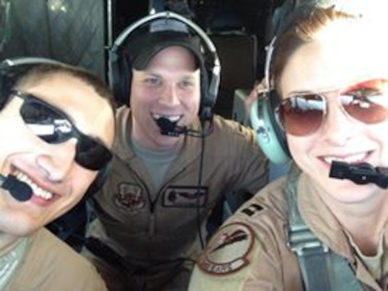 First Lt. Ryan Cobb, center, 384th Air Refueling Squadron navigator, poses for a photo, April 2014 during a deployment. (Courtesy photo)