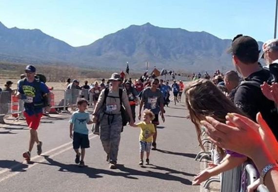 Tech. Sgt. Julia Getter, 53rd Test Support Squadron weapons evaluation group logistics manager, crosses the finish line of the Bataan Memorial Death March with her kids. This was Getter's fifth time taking part in the grueling 26.2-mile march.  (Courtesy photo)
