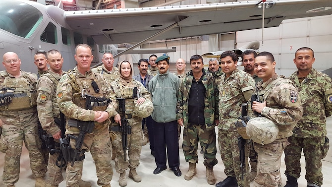 Train, Advise, Assist Command-Air (TAAC-Air) maintenance advisors pose with some of their Afghan air force maintenance counterparts at an aircraft hangar at Hamid Karzai International Airport, Kabul, Afghanistan, March 2016. TAAC-Air coalition advisors work daily to train, advise, and assist their Afghan partners to develop a professional, capable, and sustainable air force. (U.S. Air Force photo by Staff Sgt. Steven Marquez/released)