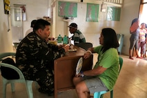 "Armed Forces of the Philippine Maj. Paul Castillo gives a health screening to a woman during a cooperative health engagement during exercise Balikatan in Cagayancillo, Philippines April 10, 2016.  Balikatan, which means ""shoulder to shoulder"" in Filipino, is an annual bilateral training exercise focused on improving the ability of Philippine and U.S. military forces to work together during planning, contingency and humanitarian assistance and disaster relief operations."