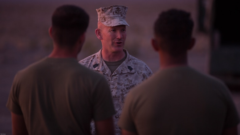 Sergeant Maj. William Sowers, 1st Marine Division Sergeant Major, talks to Marines of 7th Marine Regiment during the regiment's Combined Arms Live Fire Exercise at Marine Corps Air Ground Combat Center, April 5, 2016. CALFEX served as the kinetic portion of Desert Scimitar 16, an annual 1st Marine Division training evolution.
