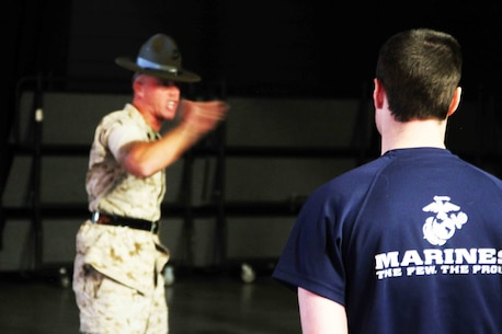 A poolee with Marine Corps Recruiting Station Twin Cities stands at attention as one of the three drill instructors in attendance educate the future Marines on customs and courtesies at the RS Twin Cities Family Night, April 9. During the family night, drill instructors, RS staff and guest speakers informed families on what to expect at recruit training.