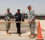 "CAMP VICTORY, IRAQ – (center) U.S. Marine 2nd Lt. Ahmed Khalil, then the operations manager for Al-Andalus Company, participates in a ribbon cutting ceremony for successfully completing ""Victory Base Complex Waste water treatment plant located in Camp Victory, Iraq 2007. The project added 2 million gallons of treated water to the effluent available to farmlands and inhabitants living near the canal. Khalil used his lingual skills and business acumen to work with the US military to accomplish numerous projects in Iraq.  (Courtesy photo by 2nd. Lt. Ahmed Khalil/Released)"