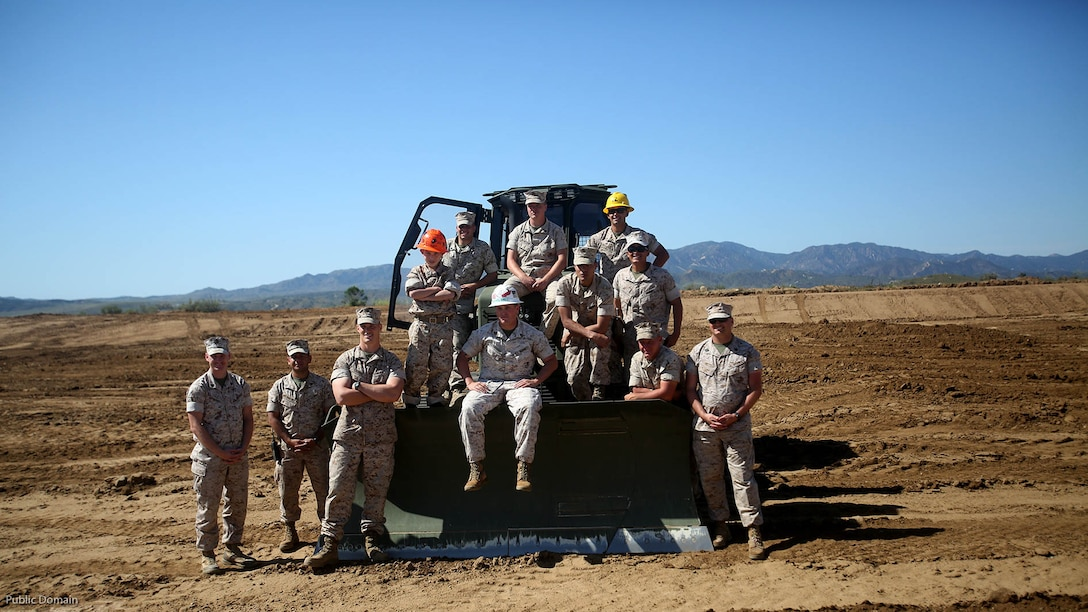 Nathan Aldaco, a 12 year-old boy with hypoplastic left heart syndrome, poses for a photo with heavy equipment operators during a Make-A-Wish event supported by 7th Engineer Support Battalion, 1st Marine Logistics Group, aboardMarine Corps Base  Camp Pendleton, California, March 24, 2016. Marines with 7th ESB and Explosive Ordnance Disposal helped to make Nathan's wish of training with Marines come true by demonstrating the capabilities of their EOD robots and detonating TNT, C4, dynamite and blasting caps, while the heavy equipment operators gave him the opportunity to ride the D7 dozer and the excavator, in which he dug a pit, built a berm, and broke several large tree trunks.