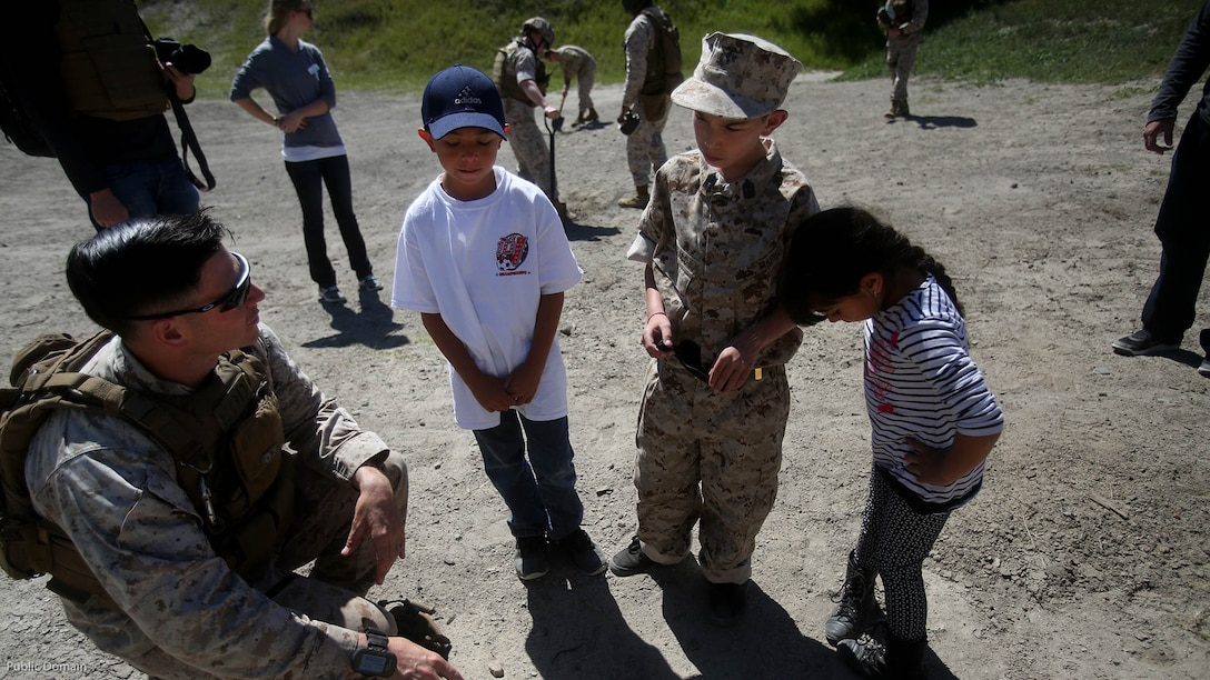 Nathan Aldaco, a 12 year-old boy with hypoplastic left heart syndrome, along with his brother and sister learn about TNT during a Make-A-Wish event supported by 7th Engineer Support Battalion, 1st Marine Logistics Group, at Marine Corps base Camp Pendleton, Calif., March 24, 2016. Marines with 7th ESB and Explosive Ordnance Disposal helped to make Nathan's wish of training with Marines come true by demonstrating the capabilities of their EOD robots and detonating TNT, C4, dynamite and blasting caps, while the heavy equipment operators gave him the opportunity to ride the D7 dozer and the excavator, in which he dug a pit, built a berm, and broke several large tree trunks.