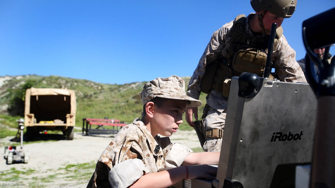 Nathan Aldaco, a 12 year-old boy with hypoplastic left heart syndrome, controls a Pacbot during a Make-A-Wish event supported by 7th Engineer Support Battalion, 1st Marine Logistics Group, at Marine Corps Base Camp Pendleton, California, March 24, 2016. Marines with 7th ESB and Explosive Ordnance Disposal helped to make Nathan's wish of training with Marines come true by demonstrating the capabilities of their EOD robots and detonating TNT, C4, dynamite and blasting caps, while the heavy equipment operators gave him the opportunity to ride the D7 dozer and the excavator, in which he dug a pit, built a berm, and broke several large tree trunks.
