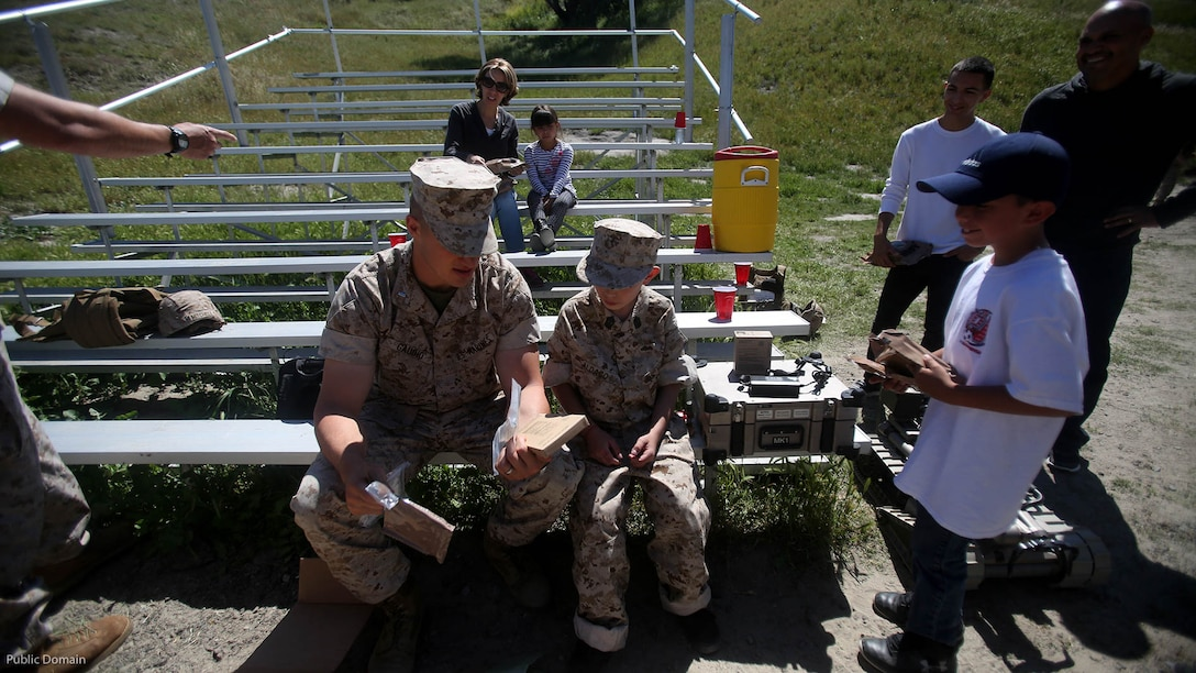 Nathan Aldaco, a 12 year-old boy with hypoplastic left heart syndrome, prepares to eat field rations with 1st Lt. Ernest Gaudio during a Make-A-Wish event supported by 7th Engineer Support Battalion, 1st Marine Logistics Group, at Marine Corps Base Camp Pendleton, California, March 24, 2016. Gaudio is a platoon commander with Bravo Company, 7th ESB, 1st MLG. Marines with 7th ESB and Explosive Ordnance Disposal helped to make Nathan's wish of training with Marines come true by demonstrating the capabilities of their EOD robots and detonating TNT, C4, dynamite and blasting caps, while the heavy equipment operators gave him the opportunity to ride the D7 dozer and the excavator, in which he dug a pit, built a berm, and broke several large tree trunks.