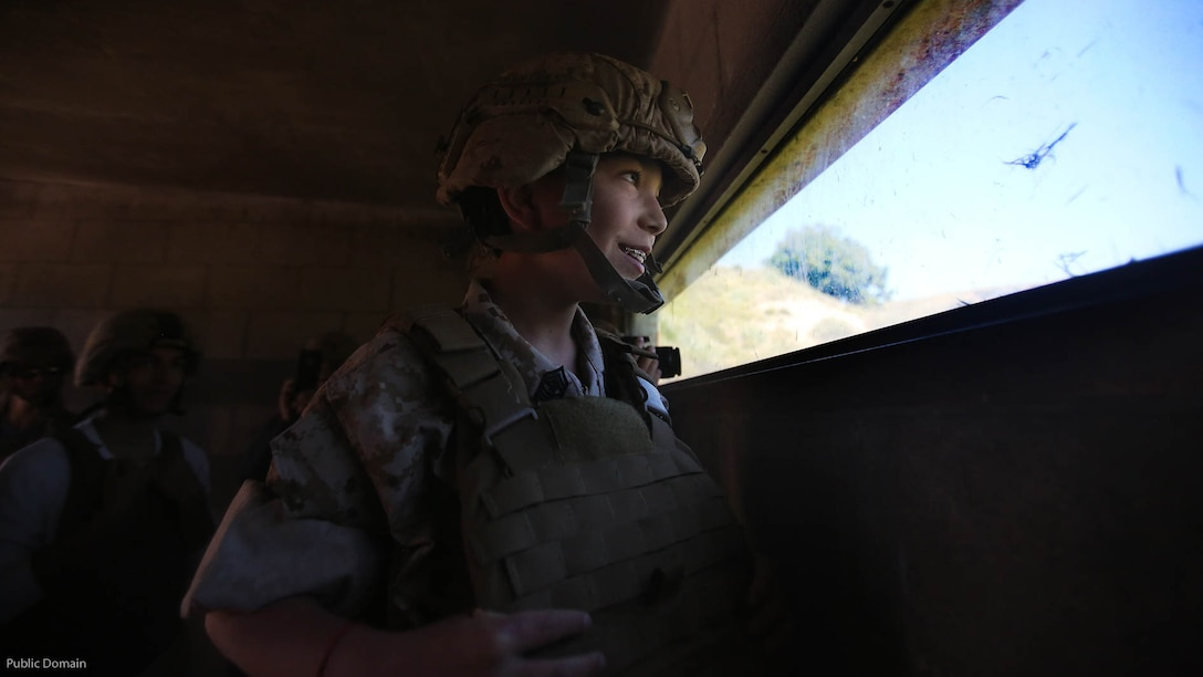 Nathan Aldaco, a 12 year-old boy with hypoplastic left heart syndrome, looks out of a bunker during a Make-A-Wish event supported by 7th Engineer Support Battalion, 1st Marine Logistics Group, at Marine Corps Base Camp Pendleton, California, March 24, 2016. Marines with 7th ESB and Explosive Ordnance Disposal helped to make Nathan's wish of training with Marines come true by demonstrating the capabilities of their EOD robots and detonating TNT, C4, dynamite and blasting caps, while the heavy equipment operators gave him the opportunity to ride the D7 dozer and the excavator, in which he dug a pit, built a berm, and broke several large tree trunks.