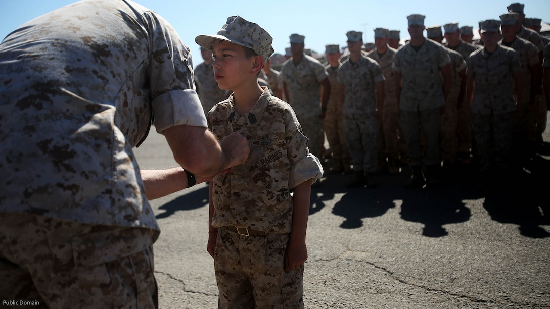 Nathan Aldaco, a 12 year-old boy with hypoplastic left heart syndrome, stands at attention as Col. Jaime O. Collazo pins on the Master EOD badge during a Make-A-Wish event supported by 7th Engineer Support Battalion, 1st Marine Logistics Group, at Marine Corps Base Camp Pendleton, California, March 24, 2016. Collazo is the 1st MLG chief of staff. Marines with 7th ESB and Explosive Ordnance Disposal helped to make Nathan's wish of training with Marines come true by demonstrating the capabilities of their EOD robots and detonating TNT, C4, dynamite and blasting caps, while the heavy equipment operators gave him the opportunity to ride the D7 dozer and the excavator, in which he dug a pit, built a berm, and broke several large tree trunks.