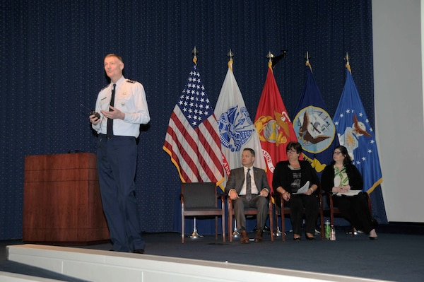 DLA Director Air Force Lt. Gen. Andy Busch delivers his opening remarks to employees at the Process Excellence All-Hands Town Hall April 12. Seated left to right: Marcus Bowers, Billie Sue Goff and Heather Vickers.