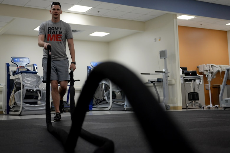 U.S. Marine Corps Staff Sgt. Darien Darland, Keesler Marine Detachment weather instructor, swings battle ropes while balancing on one leg in the physical therapy department, April 7, 2016, Keesler Air Force Base, Miss. When recovering from a leg injury, balancing on one leg can be difficult. As clients progress in their therapy, technicians increase exercise difficulty. Incorporating battle ropes into a single leg stability exercise adds an extra challenge to the client. (Air Force Photo by Airman 1st Class Travis Beihl)