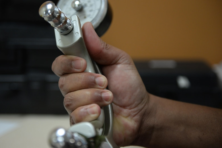 Wayne Williams, 81st Medical Support Squadron bio-medical technician, squeezes a grip strength machine in the physical therapy department April 7, 2016, Keesler Air Force Base, Miss. This machine is used to measure the maximum hand strength on both the affected and non-affected limb. Physical medicine technicians then use this number as a baseline to work toward balancing the strength in both limbs. (Air Force Photo by Airman 1st Class Travis Beihl)