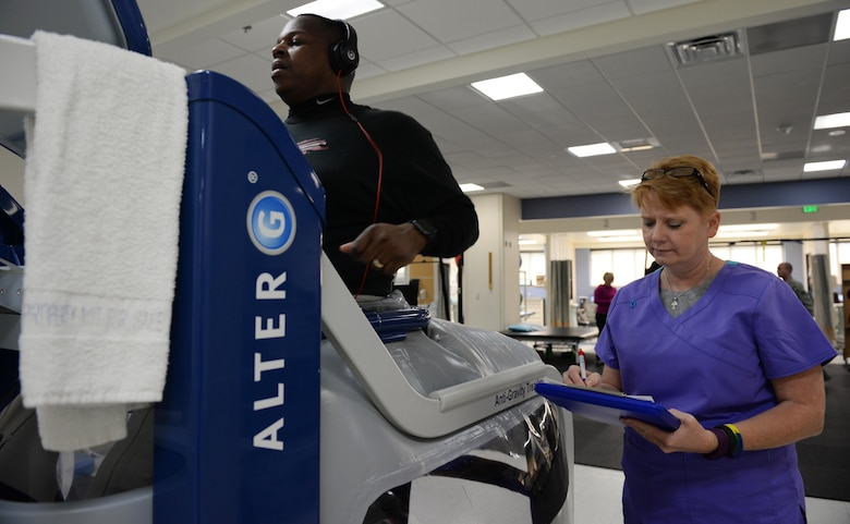 Sharay Windham, 81st Medical Support Squadron licensed physical therapist assistant, takes notes as Master Sgt. Byron Self, 81st Security Forces Squadron flight chief, runs on an anti-gravity treadmill in the Physical Therapy department, April 6, 2016, Keesler Air Force Base, Miss. The anti-gravity treadmill is used to help rehabilitate clients who have injuries to their lower limbs by decreasing the amount of weight on the client's joints which helps with recovery after injury or surgery. (Air Force Photo by Airman 1st Class Travis Beihl)