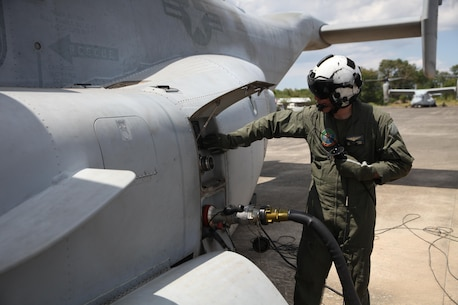 U.S. Marine Sgt. Anthony Dicola makes adjustments to an MV-22B Osprey while it pumps fuel at an aerial delivery ground refueling station to refuel a U.S. Army UH-60 Black Hawk during Balikatan 16, in San Fernando, Philippines, April 12, 2016. Dicola is from Omaha Nebraska and a MV-22 crew chief for Marine Medium Tilt-rotor Squadron 262, Marine Aircraft Group 36, 1st Marine Aircraft Wing, III Marine Expeditionary Force. After establishing the ADGR, the Marines of VMM-262 refueled multiple U.S. Army aircrafts from Bravo 3-25, Aviation Regiment via the MV-22B Osprey.