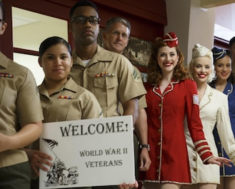 Marines with Marine Forces Reserve and the Victory Belles, the National World War II Museum's vocal trio, wait for veterans participating in the Soaring Valor program to exit the terminal at Louis Armstrong New Orleans International Airport, April 13, 2016. The Soaring Valor program was created by actor Gary Sinise to honor veterans of World War II for their sacrifices and to give them a special tour of the National World War II Museum. (U.S. Marine Corps photo by Cpl. Ian Leones/ Released)