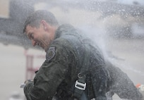 Col. Aaron Steffens, 57th Wing vice commander, is showered with champagne and water as he exits his aircraft after his fini flight at Nellis Air Force Base, Nev., April 8, 2016. As vice commander of the 57th Wing, Steffens was instrumental in managing all flying operations at Nellis AFB and conducts advanced aircrew, space, logistics and command and control training through the USAF Weapons School, Red Flag and Green Flag exercises. (U.S. Air Force photo by Airman 1st Class Nathan Byrnes)