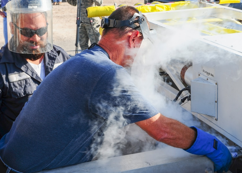 Technicians from the 846th Test Squadron at Holloman Air Force Base, N.M., pump liquid helium into a test sled here Aug. 18, 2015. This sled system runs on four super-conducting magnets that need to be cooled down to a few degrees above absolute zero to ensure the smoothest ride possible. (U.S. Air Force photo by Airman 1st Class Randahl J. Jenson)
