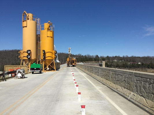 The concrete batch plant is in the foreground atop the Rough River Lake Dam, Ky. The white PVC casings are installed through the embankment to allow drilling and grouting in the rock foundation.