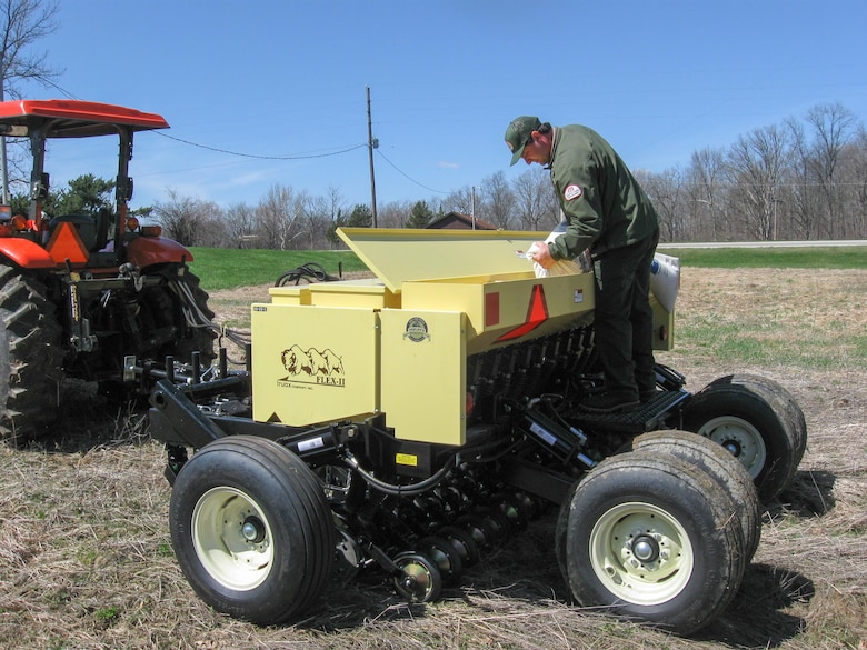 John Scheiber, Salamonie Lake Project Manager, pours prairie grass seed into the no-till drill specifically designed to plant prairie species. The drill was purchased using Handshake Partnership funding along with funding from the National Wild Turkey Federation.