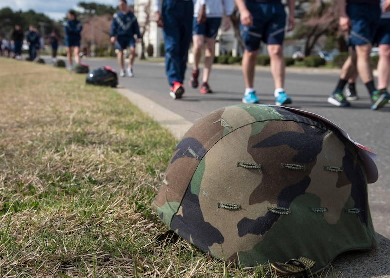 """Military helmets line Risner Circle during Resilient Airman Day at Misawa Air Base, Japan, April 15, 2016. During the """"Silent Walk"""" portion of the day, Misawa military members passed by helmets topped with red cards describing sexual assaults occurring during fiscal year 2015 and 2016. The purpose of this event was to highlight the necessity of caring for one's wingman and bring the severity of the issue home. (U.S. Air Force photo by Airman 1st Class Jordyn Fetter)"""