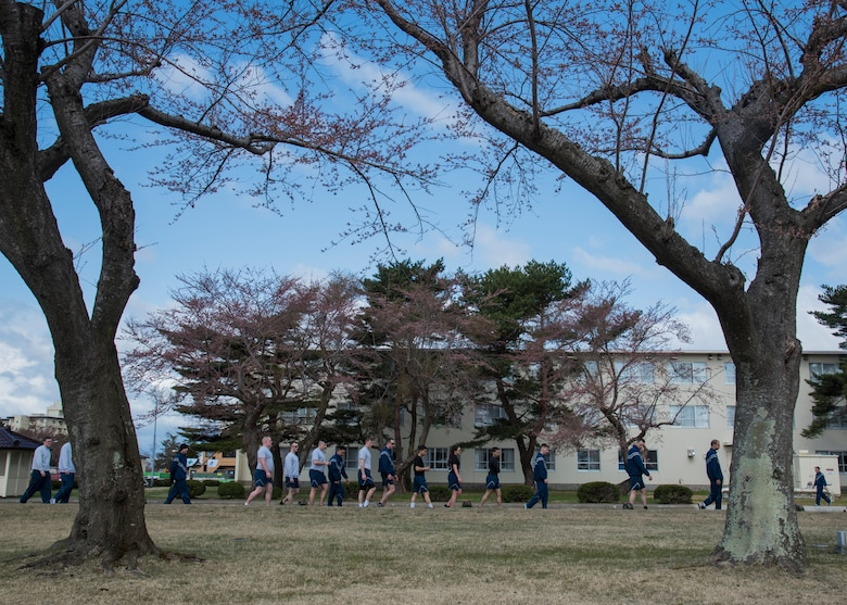 """U.S. Air Force Airmen walk along Risner Circle during Resilient Airman Day at Misawa Air Base, Japan, April 15, 2016. After completing a 5K run, participants partook in a """"Silent Walk"""" where helmets topped with red cards describing sexual assaults occurring during fiscal year 2015 and 2016 were placed. The event's goal was to show this crime is an issue, even at Misawa, and to emphasize the necessity of caring for one's wingman. (U.S. Air Force photo by Airman 1st Class Jordyn Fetter)"""
