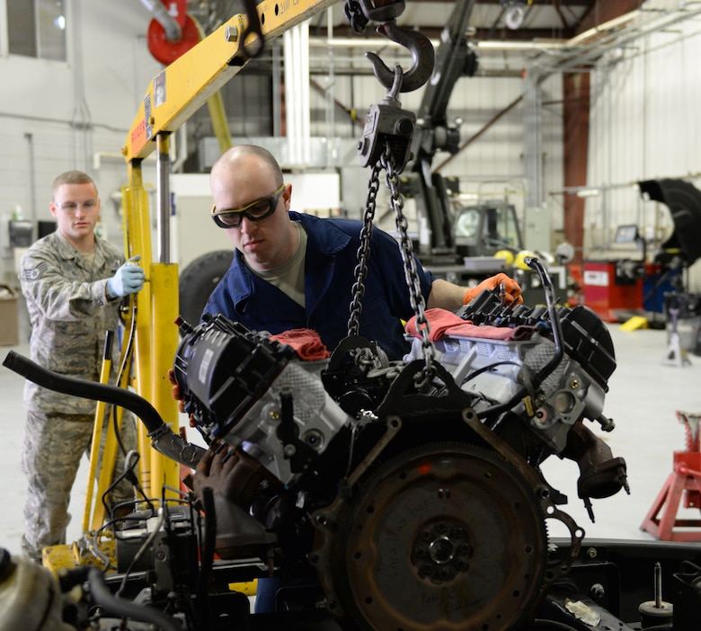 U.S. Air Force Staff Sgt. Chris Wood, (left) and Airman 1st Class Patrick Clifford move a new  Ford 5.4 liter V8 engine in a 2008 Ford F-150 pickup truck, April 14, 2016, Pease Air National Guard Base, N.H. The Airmen are special purposes vehicle technicians assigned to the Vehicle Maintenance Branch, 157th Logistics Readiness Squadron, New Hampshire Air National Guard. (U.S. Air National Guard photo by Staff Sgt. Curtis J. Lenz)