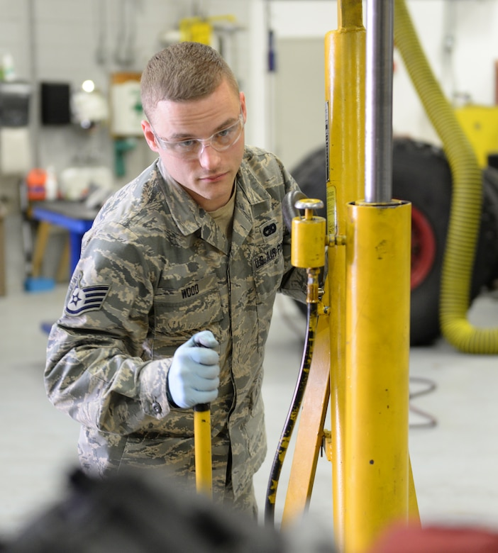 U.S. Air Force Staff Sgt. Chris Wood, 157th Logistics Readiness Squadron special purpose vehicle technician, uses a floor jack to lift a Ford 5.4 liter V8 engine in a 2008 Ford F-150 pickup truck, April 14, 2016, Pease Air National Guard Base, N.H. (U.S. Air National Guard photo by Staff Sgt. Curtis J. Lenz)