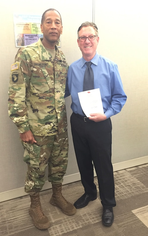 DLA Troop Support Commander Army Brig. Gen. Charles Hamilton presents Evan Eisenberg with a Commander's Coin and congratulations letter March 31, 2016 for earning the DLA Acquisition Professional Supporting Small Business award. Eisenberg was selected for the award for planning and awarding two contracts for the Navy Working Uniform to small businesses in fiscal 2015.