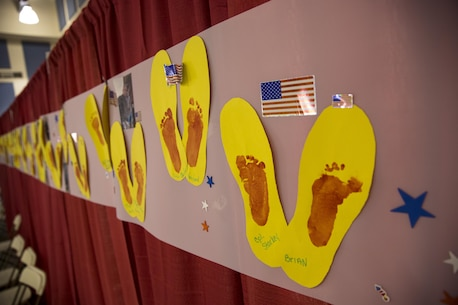 Footprints created by military children at the Combat Center Armed Services YMCA are displayed during the 6th Annual Veteran's Expo at the Riverside County Fairgrounds in Indio, Calif., April 2, 2016. The children traced their active duty parent's boot and used their feet to paint their prints in the center. (Official Marine Corps photo by Lance Cpl. Levi Schultz/Released)