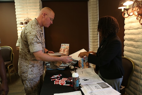 U.S. Marine Gunnery Sgt. Raul Padronmartin reads a pamphlet at a family advocacy booth during the 101 days of summer campaign kick-off event aboard Camp Pendleton, Calif., April 11, 2016. Padronmartin is a maintenance chief with 1st Maintenance Battalion, 1st Marine Logistics Group.  Leaders within 1st MLG stressed the importance of taking care of their own and taking the time to know their Marines. Various organizations directed at supporting and enriching service members' lives had pamphlets and helpful information readily available for all who attended. (U.S. Marine Corps photo by Sgt. Laura Gauna/released)