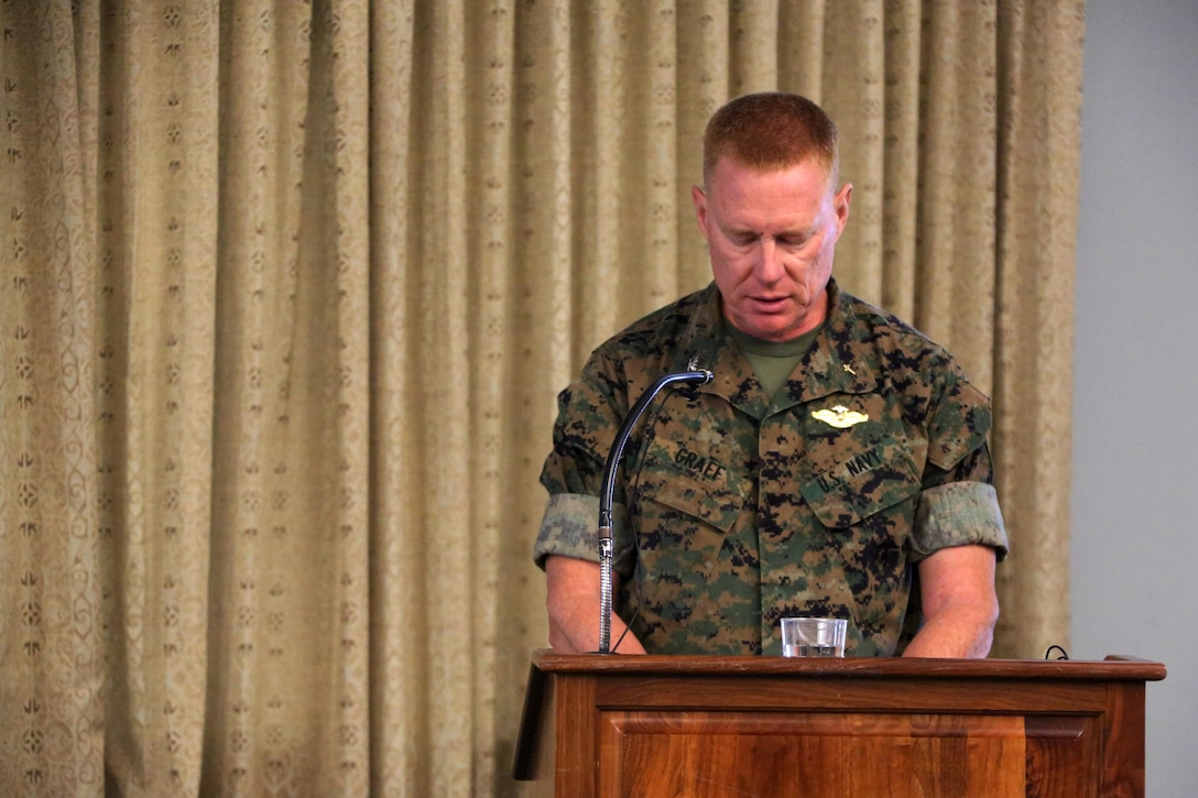 Navy Capt. Russell Graef conducts a prayer during a volunteer appreciation award ceremony at Marine Corps Air Station Cherry Point, N.C., April 12, 2016. The award ceremony was held to recognize the more than 90,000 volunteer hours collectively accomplished by members of the air station community. Senior leaders represented their units along with DOD employees and service family volunteers as they received individual recognition for their volunteer efforts and the positive impact they have on the air station. Graef is the 2nd Marine Aircraft Wing chaplain. (U.S. Marine Corps photo by Cpl. N.W. Huertas/Released)