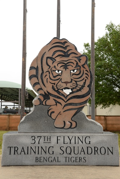 A statue and flagpoles depicting the 37th Flying Training Squadron mascot sits outside the building April 12 at Columbus Air Force Base, Mississippi. Before it was a training squadron, it was first established as the 37th Pursuit Squadron in January 1941, where it flew the P-38 Lightning I. (U.S. Air Force photo/Airman 1st Class John Day)