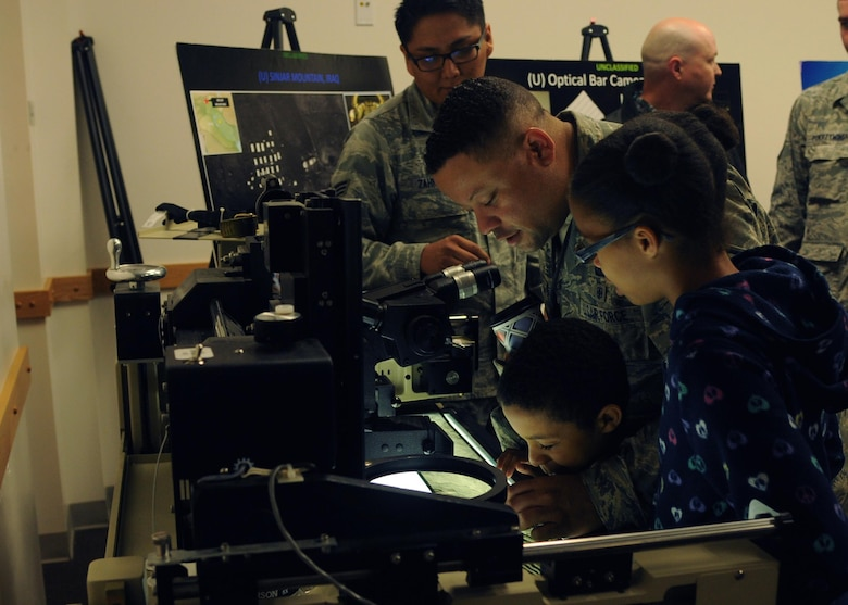 Master Sgt. Charles examines optical bar camera film with his children at an open house for the 548th Intelligence, Surveillance and Reconnaissance Group at Beale Air Force Base, April 13, 2016. The 548th ISR Group opened their doors, allowing family members to get an inside look at the work their Airmen do on a daily basis. (U.S. Air Force photo by Airman 1st Class Jessica B.  Nelson/Released)