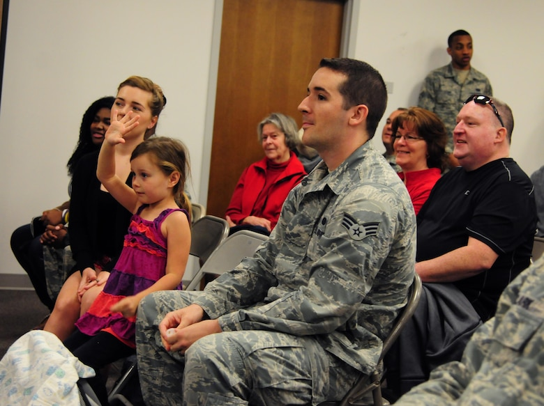 """Aaliayah raises her hand to indicate that it's her birthday during an open house hosted by the 548th Intelligence, Surveillance and Reconnaissance Group at Beale Air Force Base, April 13, 2016.  Members of the audience joined Col. Drew Taylor in singing """"Happy Birthday"""" to Aaliayah and presented her with a cake. (U.S. Air Force photo by Staff Sgt. Zachary Vucic)"""