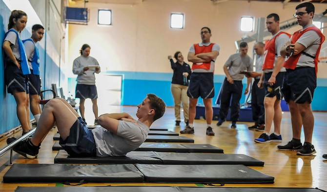 Airman 1st Class Trandon Sowell, 721st Aerial Port Squadron passenger service agent and physical training leader, demonstrates how to do a correct sit-up before a fitness assessment April 12, 2016, at Ramstein Air Base, Germany. Airmen who train to become a physical training leader are augmented to assist with running fitness assessments. (U.S. Air Force photo/Senior Airman Larissa Greatwood)