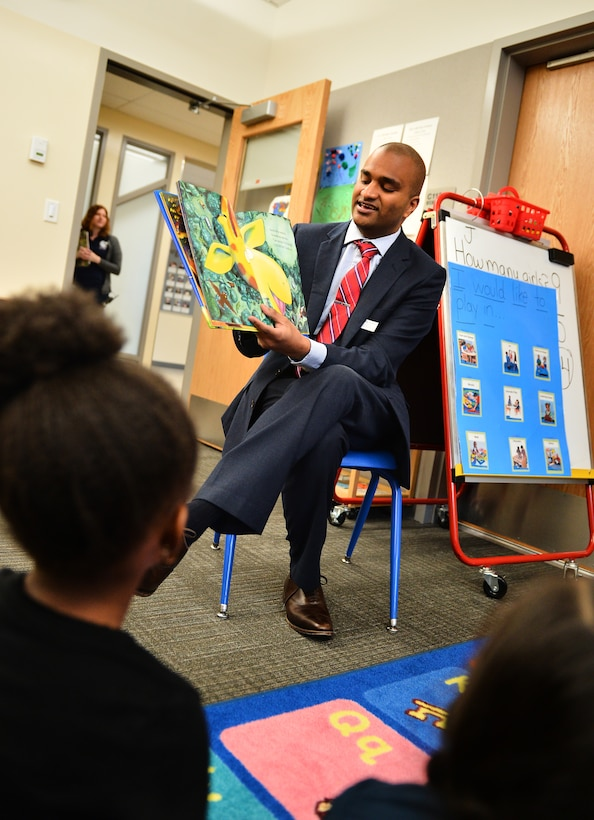 """Jason Thomas, program coordinator for Governor John Hickenlooper's office, reads """"Giraffes Can't Dance"""" to children at Edna and John W. Mosley P-8 school April 15, 2016, in Aurora, Colo. Thomas joined others as part of the One Book 4 Colorado program, which is designed to encourage children to read. (U.S. Air Force photo by Staff Sgt. Darren Scott/Released)"""