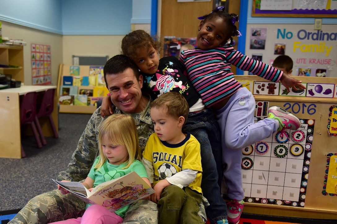 Col. John Wagner, 460th Space Wing commander, poses with children April 13, 2016, at the Crested Butte Child Development Center on Buckley Air Force Base, Colo. One Book 4 Colorado is a program intended to close the vocabulary gap between lower and higher income families. (U.S. Air Force photo by Airman 1st Class Gabrielle Spradling/Released)