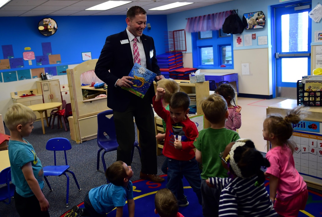 Richard Sandrock, Community Partnerships deputy director for Colorado Gov. John Hickenlooper, dances with children April 13, 2016, at the Crested Butte Child Development Center on Buckley Air Force Base, Colo. Sandrock visited the CDC to read and promote One Book 4 Colorado, which aims to provide children with early literacy skills. (U.S. Air Force photo by Airman 1st Class Gabrielle Spradling/Released)